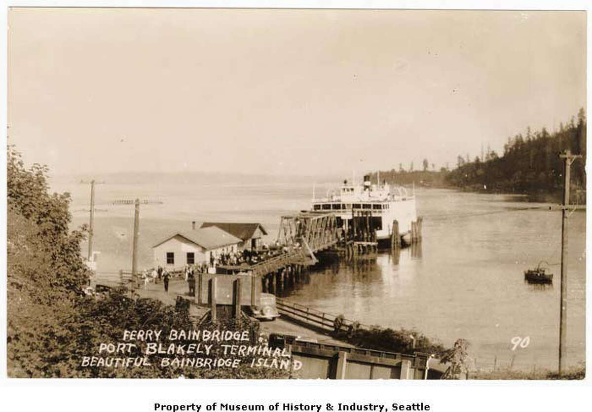"""""""When Port Blakely, Washington, was a bustling lumber mill and shipbuilding town, it had regular steamer and ferry service. Even after the shipyard moved in 1903 and the sawmill closed down in 1922, ferry service continued. The """"Bainbridge"""" one of the area's first auto ferries, had the Seattle to Port Blakely run from 1924 to 1937. This photographic postcard, probably made sometime in the 1920s, shows the ferry """"Bainbridge"""" at the Port Blakely terminal. When the """"Bainbridge"""" stopped running in 1937, the town lost its direct ferry connection to Seattle."""" -MOHAI. Photo courtesy MOHAI, Ziegler and Rankin Families Photographs, image number 1977.6486.11."""