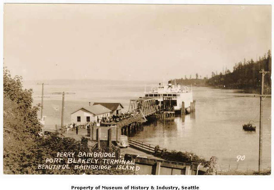 """""""When Port Blakely, Washington, was a bustling lumber mill and shipbuilding town, it had regular steamer and ferry service. Even after the shipyard moved in 1903 and the sawmill closed down in 1922, ferry service continued. The """"Bainbridge"""" one of the area's first auto ferries, had the Seattle to Port Blakely run from 1924 to 1937. This photographic postcard, probably made sometime in the 1920s, shows the ferry """"Bainbridge"""" at the Port Blakely terminal. When the """"Bainbridge"""" stopped running in 1937, the town lost its direct ferry connection to Seattle."""" -MOHAI. Photo courtesy MOHAI, Ziegler and Rankin Families Photographs, image number 1977.6486.11. Photo: Courtesy MOHAI"""