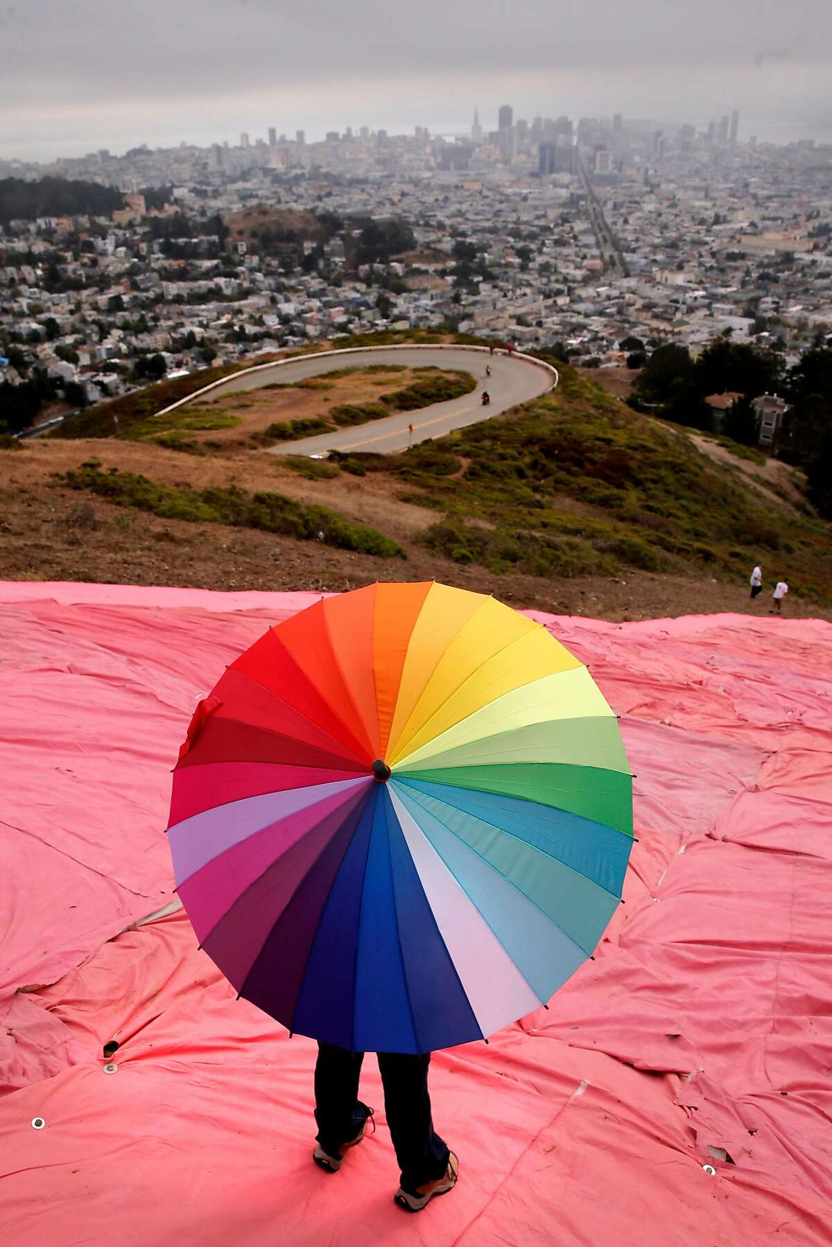 Heather Raich, of San Francisco looks out over the city as volunteers install the huge pink triangle atop Twin Peaks for all to see, representing the violence aimed at the LGBT community both in the past and today during Pride Weekend events as seen on Sat. June 27, 2015, in San Francisco, Calif.