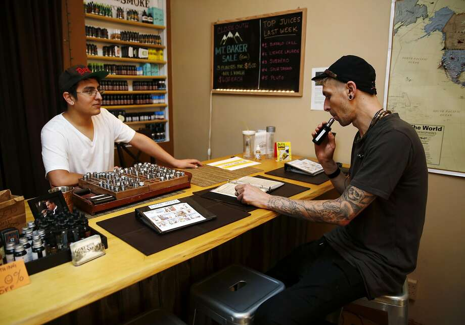 Employee Jesse Leanos (left) shows products to Paul Victor at Gone With the Smoke. Photo: Connor Radnovich, The Chronicle