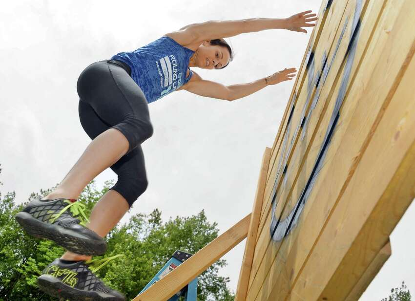 Melissa Manzer, co-owner of CrossFit Round Lake climbs over a wall at the sports facility Wednesday June 8, 2016 in Round Lake, NY. (John Carl D'Annibale / Times Union)