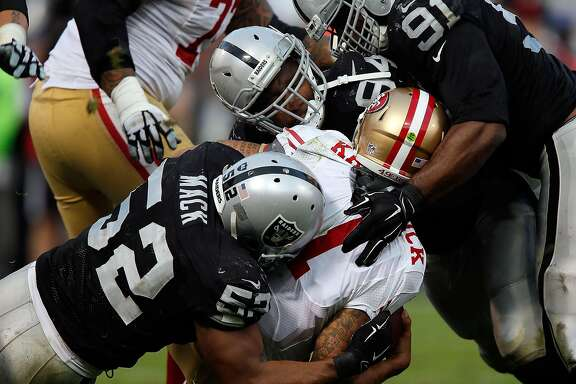 OAKLAND, CA - DECEMBER 07:  Justin Tuck #91 of the Oakland Raiders, Antonio Smith #94 of the Oakland Raiders, Khalil Mack #52 of the Oakland Raiders sack Colin Kaepernick #7 of the San Francisco 49ers in the fourth quarter at O.co Coliseum on December 7, 2014 in Oakland, California.  (Photo by Brian Bahr/Getty Images)