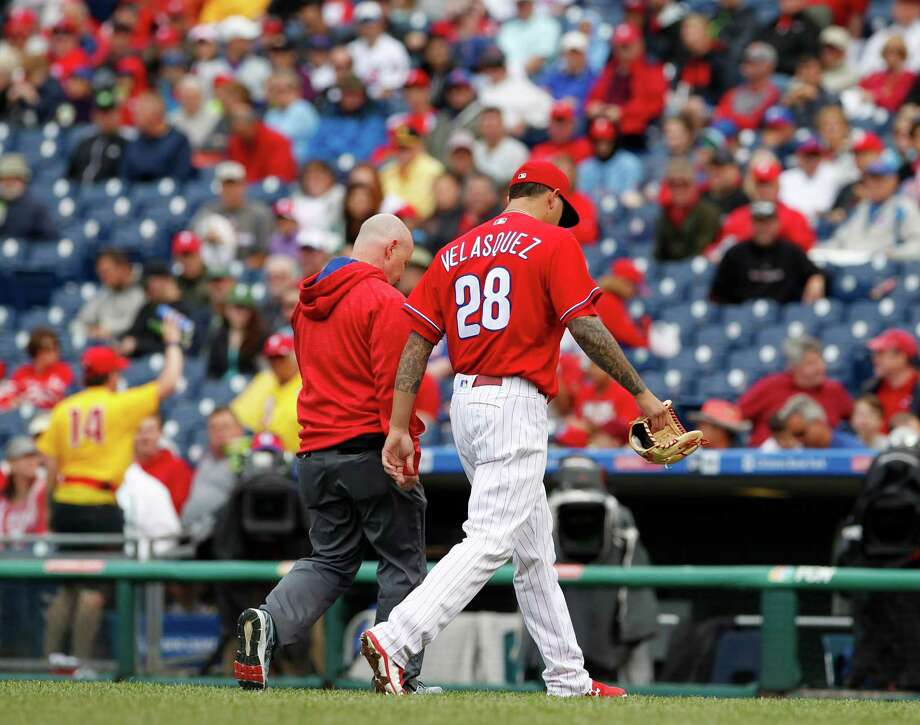 The Phillies' Vince Velasquez takes part in the scene every pitcher hopes to avoid - leaving the field with a trainer after an abbreviated outing. Photo: CHARLES FOX, MBR / Philadelphia Inquirer