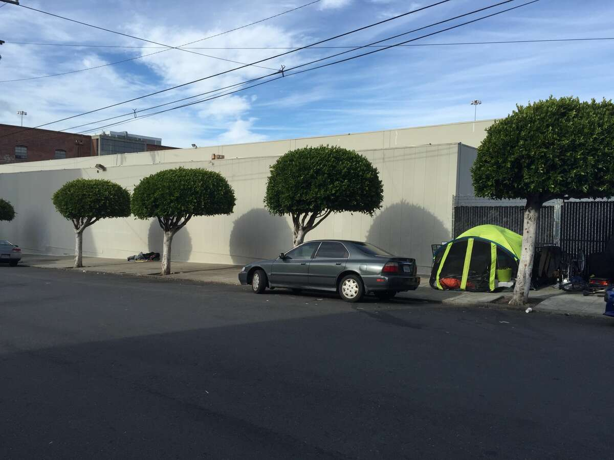 The rear of Bonhams Auction House in San Francisco shows a homeless man sleeping against the building, at left, and a tent set up along the fence of a parking lot on Utah Street.