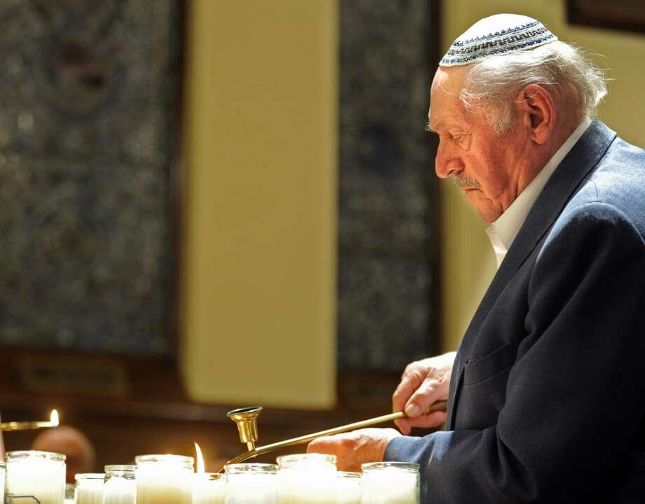 Holocaust survivor Mike Hirsch lights a candle during Fairfield's annual Holocaust Commemoration at First Church Congregational. Photo: Autumn Driscoll / Connecticut Post