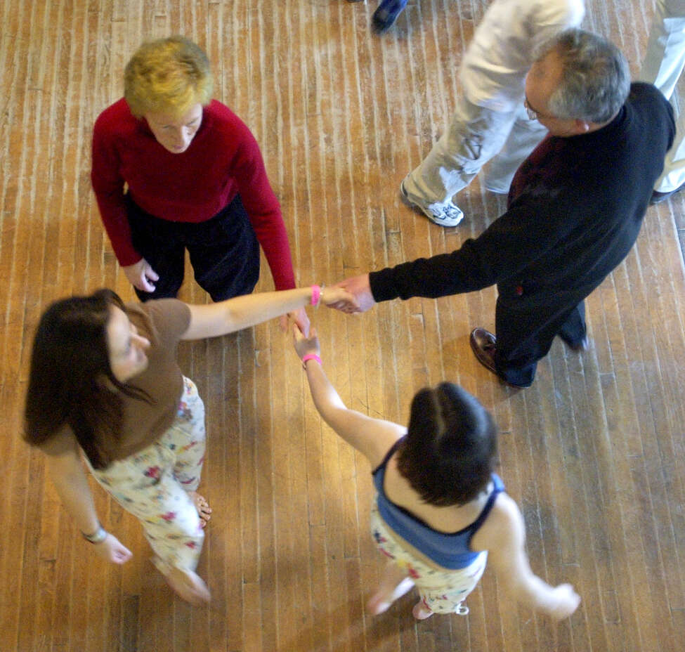 TIMES UNION STAFF PHOTO WILL WALDRON--Dance Flurry, dancers cross hands during a work shop entitled Contras for novices, at the Saratoga Music Hall, Saturday, February 14, 2004.