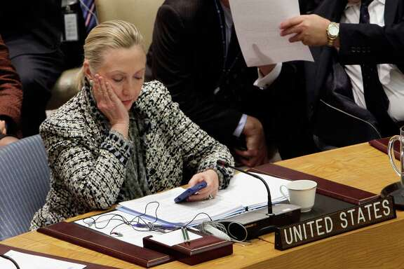 FILE - In this March 12, 2012 file photo, then-Secretary of State Hillary Rodham Clinton checks her mobile phone after her address to the Security Council at United Nations headquarters. The names of CIA personnel could have been compromised not only by hackers who may have penetrated Hillary Clinton's private computer server or the State Department system, but also by the release itself of tens of thousands of her emails.  (AP Photo/Richard Drew, File)