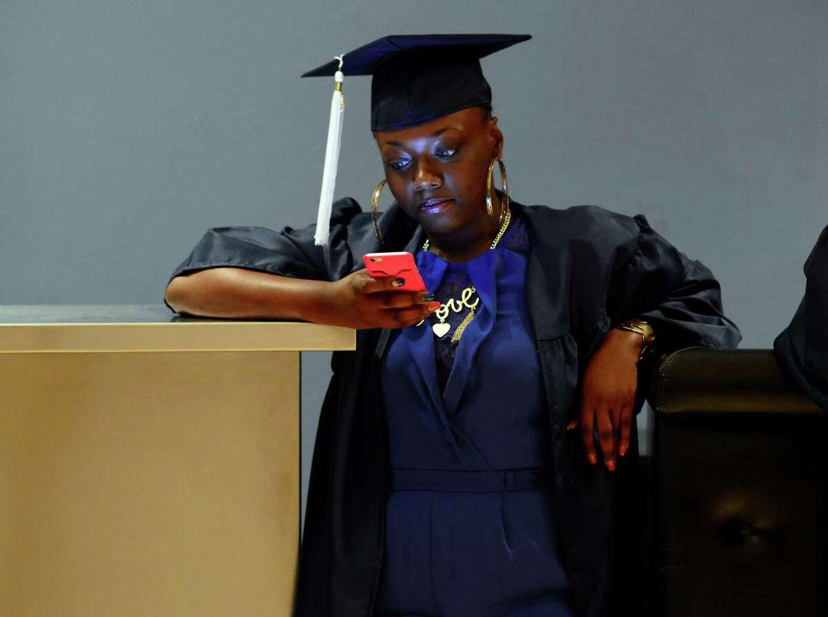 Graduate Paris Jordan uses her smart phone before the start of the Bridgeport Adult Education Graduation at the Klein Memorial Auditorium in Bridgeport, Conn., on Wednesday June 08, 2016.