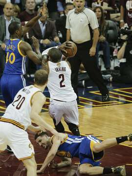 Golden State Warriors' Klay Thompson goes down while trying to chase down Cleveland Cavaliers' Kyrie Irving in the first quarter during Game 3 of the NBA Finals at The Quicken Loans Arena on Wednesday, June 8, 2016 in Cleveland, Ohio