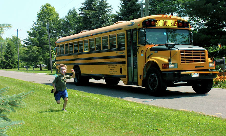 In this 2011 photo provided by Mark Barden, his son Daniel Barden runs alongside a school bus in Newtown. Daniel was among those killed during the Sandy Hook Elementary School shootings on Dec. 14, 2012, in Newtown. Photo: Mark Barden / Associated Press / Mark Barden