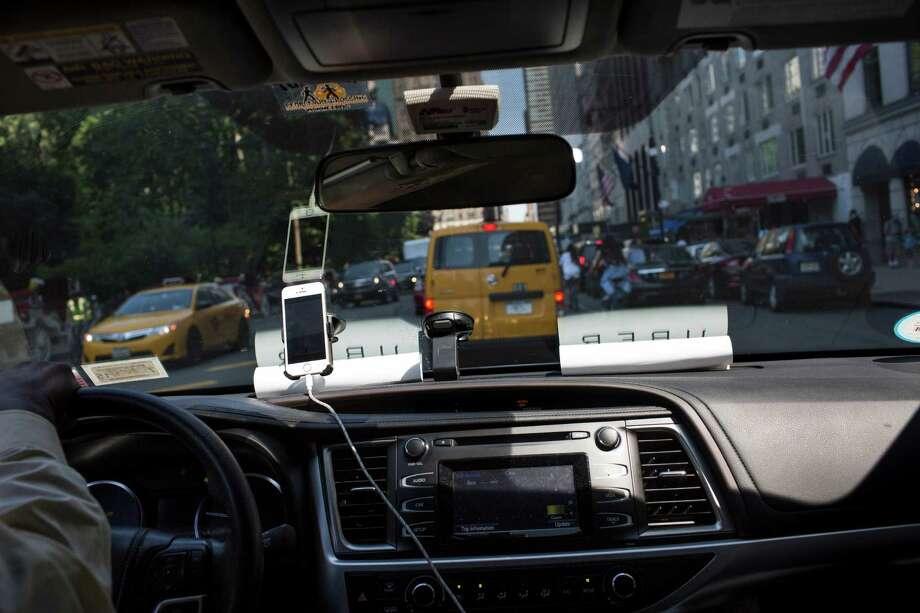 An Uber vehicle drives through New York, July 16, 2015.  (Mark Kauzlarich/The New York Times) Photo: MARK KAUZLARICH / NYTNS