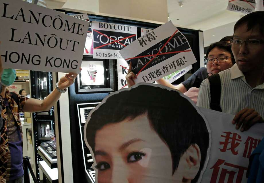 Protesters display a picture of singer Denise Ho on Wednesday at a Lancome counter in a Hong Kong department store. French cosmetics company Lancome has sparked a backlash after it canceled a promotional concert featuring a singer known for pro-democracy views. Photo: Kin Cheung, STF / Copyright 2016 The Associated Press. All rights reserved. This material may not be published, broadcast, rewritten or redistribu