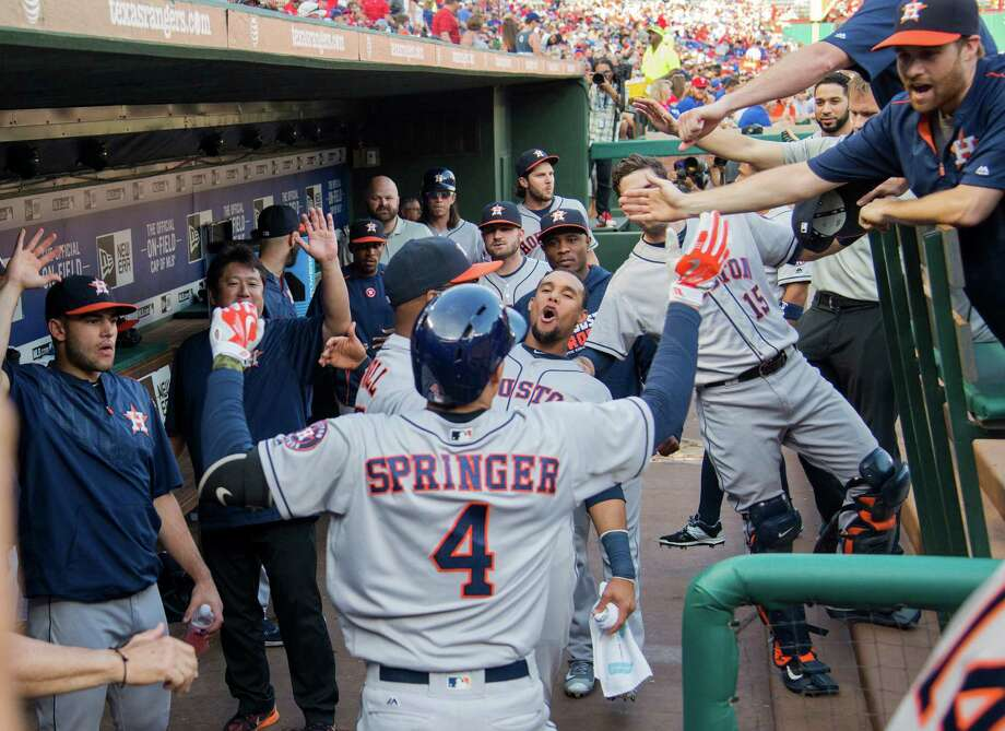 George Springer (4) gets the royal treatment from his Astros teammates after slugging a leadoff home run off Rangers pitcher Yu Darvish during the first inning of Wednesday night's 3-1 victory at Globe Life Park. Photo: Tim Sharp, FRE / FR62992 AP