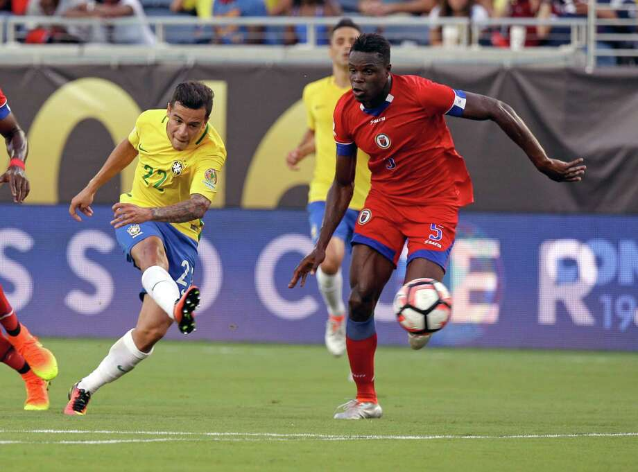 Brazil's Phillippe Coutinho fires a shot past Haiti's Romain Genevois for one of his three goals Wednesday night. Photo: John Raoux, STF / Copyright 2016 The Associated Press. All rights reserved. This material may not be published, broadcast, rewritten or redistribu