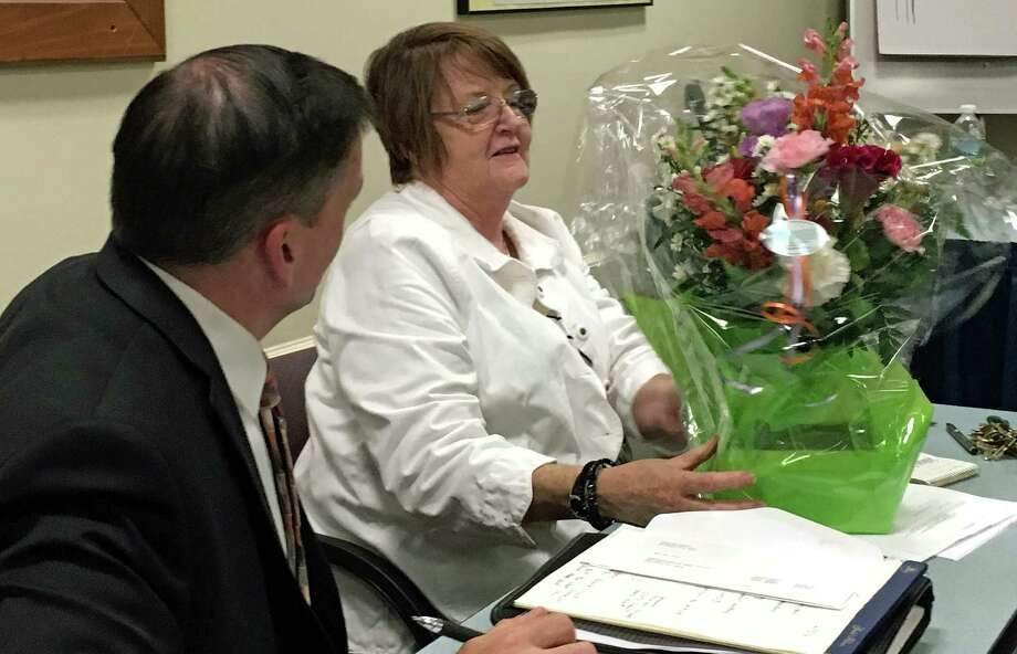As Police Chief Gary MacNamara looks on, his secretary Kathy Buzel is presented with flowers at Wednesday's Police Commission meeting. Buzel, who has worked for five police chiefs, is retiring at the end of June. Photo: Genevieve Reilly / Hearst Connecticut Media / Fairfield Citizen