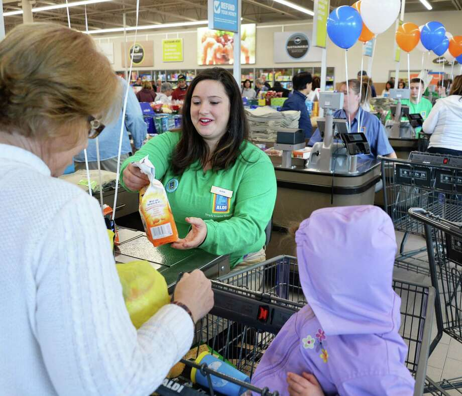 Store associate Alicia Yodis, center, helps Pam Shelly of Colonie and her granddaughter Sarah Desjardins during the grand opening of the new Aldi Store on Central Avenue Thursday June 9, 2016 in Colonie, NY.  (John Carl D'Annibale / Times Union) Photo: John Carl D'Annibale / 40036902A