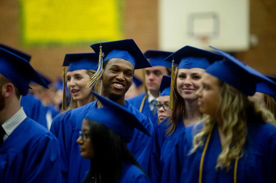 "Members of the 2016 Midland High School graduating class listens to ""Pomp and Circumstance"" while the reminder of the class walks into the gym during commencement on Friday evening. Photo: Brittney Lohmiller/Midland Daily News/Brittney Lohmiller"