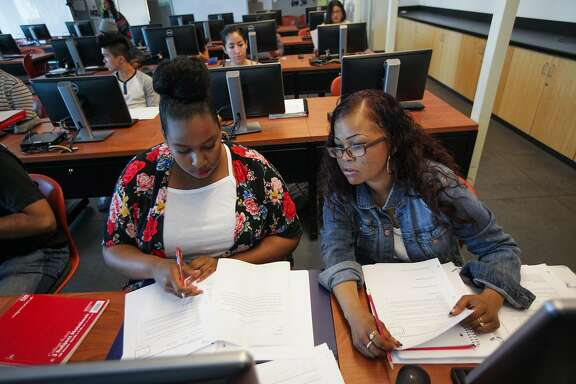 Students Angelica Grover (left) and Kim Chester (right) edit each others assignments in a statistics class at CCSF in San Francisco, California, on Friday, Aug. 28, 2015.
