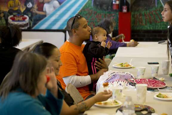 A man kisses his child's head during a community dinner at the Intertribal Friendship House on May 26, 2016 in Oakland, Calif.