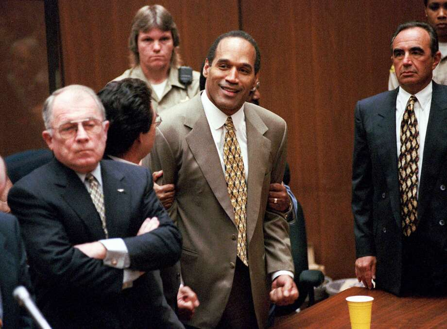 """FILE - In this Oct. 3, 1995 file photo, O.J. Simpson, center, clenches his fists in victory after the jury said he was not guilty in the murders of his ex-wife Nicole Brown Simpson and her friend Ronald Goldman in a Los Angeles courtroom as attorneys F. Lee Bailey, left, and Robert Shapiro,  right, look on. A documentary about Simpson, """"O.J.: Made in America,"""" premieres its opening two-hour segment on ABC on Saturday at 9 p.m. EDT, then moves next week to ESPN, where all five editions will air on June 14, 15, 17 and 18. (AP Photo/Los Angeles Daily News, Myung Chun, Pool) Photo: Myung Chun, POOL / LOS ANGELES DAILY NEWS POOL"""