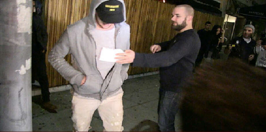 Johnny Manziel gets served with legal papers while leaving a Hollywood nightclub Wednesday night. He was recently sued over damages to a rental home allegedly caused by him and his entourage.  Photo: TMZ