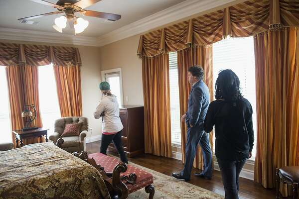 Matthew Gann, a real estate agent with Keller Williams, center, shows prospective homebuyers the bedroom of a house near Boerne, Texas, U.S., on Saturday, April 16, 2016. The National Association of Realtors is scheduled to release monthly existing home sales data on April 20. Photographer: Matthew Busch/Bloomberg *** Local Caption *** Matthew Gann