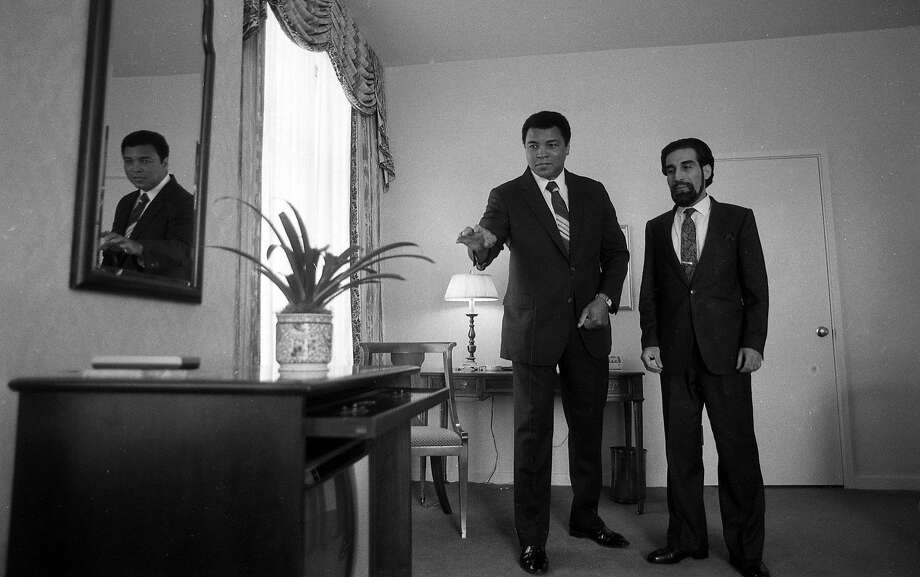Muhammad Ali, with his road manager Avudi Mahdi, claims he is about to make a vase levitate. Ali was staying at the Clift Hotel in San Francisco, and hours earlier had been declared missing by police. Photo: Deanne Fitzmaurice, The Chronicle