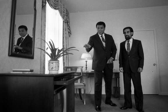 May 1, 1988: Muhammad Ali, with his road manager Avudi Mahdi, claims he is about to make a vase levitate. Ali was staying at the Clift Hotel in San Francisco, and hours earlier had been declared missing by police.