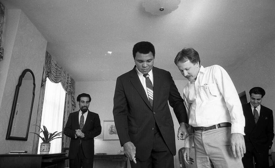 Muhammad Ali, with his road manager Avudi Mahdi (left) and San Francisco Chronicle reporter Jim Doyle (right), performs a magic trick. Ali was staying at the Clift Hotel in San Francisco, and hours earlier had been declared missing by police. Photo: Deanne Fitzmaurice, The Chronicle