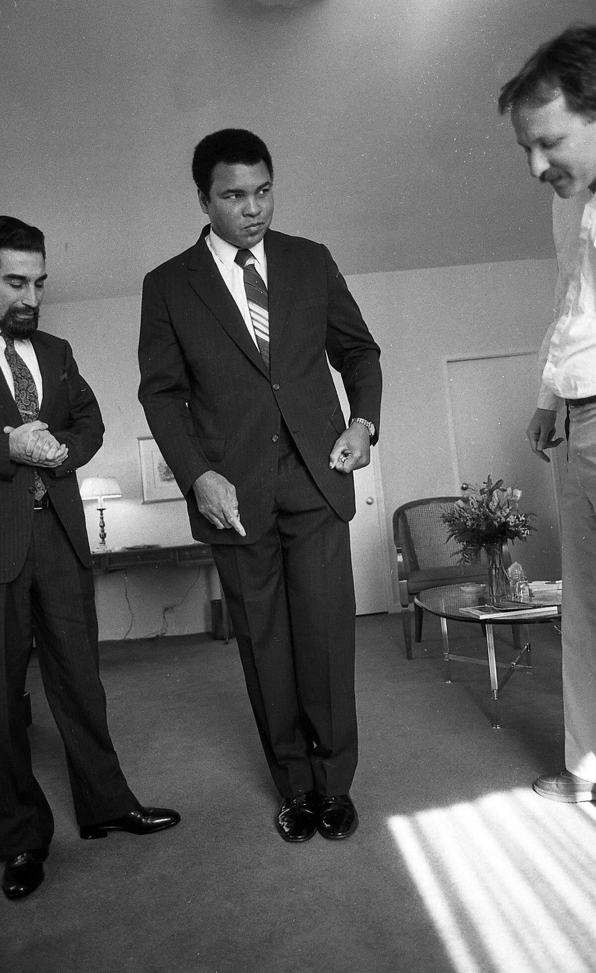 Muhammad Ali, with his road manager Avudi Mahdi (left) and San Francisco Chronicle reporter Jim Doyle (right), pretends to levitate. On May 1, 1988, Ali was staying at the Clift Hotel in San Francisco, and hours earlier had been declared missing by police.