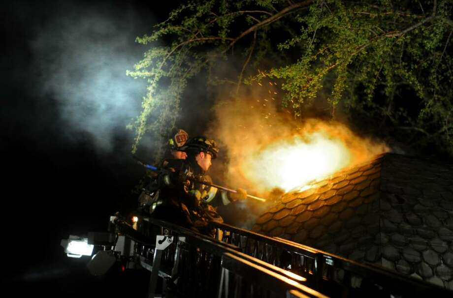 Firefighters work to put out a fire in a multi-family home on West Avenue in Bridgeport Wednesday evening Apr. 21, 2010. Photo: Autumn Driscoll / Connecticut Post