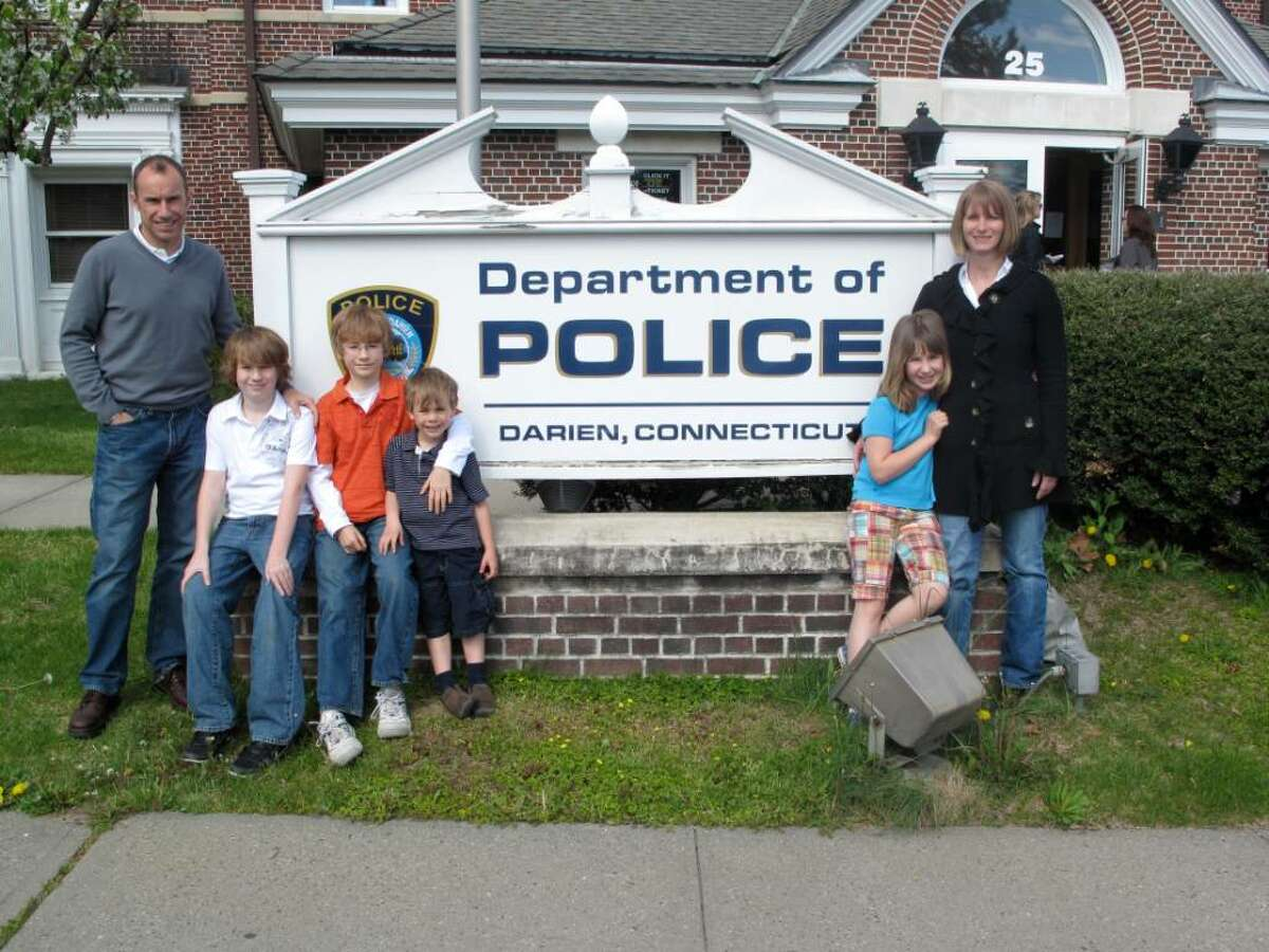 The Whittaker family visits the Darien Police Department to meet some of the officers, with whom the family will be partnering for the upcoming Make-A-Wish Foundation Police Parade. From left to right are: Martin; Luke, 12; nthan, 9; Bobby, 4; Grace, 8; and Brenda Whittaker.