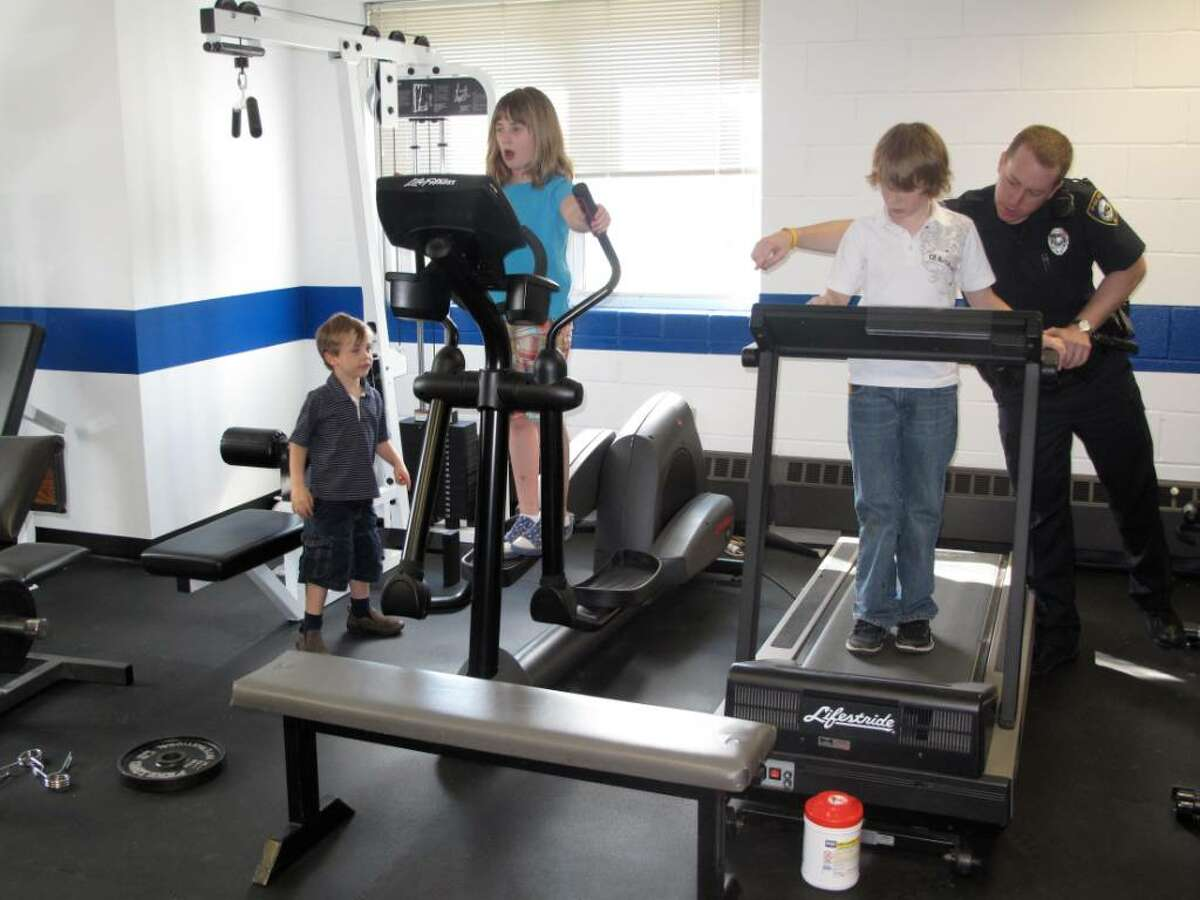 Bobby, Grace and Luke Whittaker take a turn at the fitness equipment in the police training room during their tour of the police department on Monday afternoon.