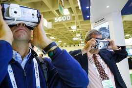 (l-r) Sergio Valentinotti and Jacob Harel use virtual reality headset devices to explore a new biology production center that Samsung is building, at the BIO convention at the Moscone Center, in San Francisco, California, on Thursday, June 9, 2016.
