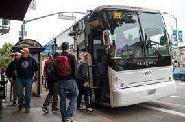 SAN FRANCISCO, CALIFORNIA - APRIL 14: Software engineers, designers and IT employees of technology companies board shuttle buses to Silicon Valley April 14, 2014 in the Mission District of San Francisco, California. Approximately 35,000 employees use shuttle buses each day to be dropped off at Google, Facebook, Yahoo and Genentech corporate headquarters in Silicon Valley. (Photo by Robert Nickelsberg/Getty Images)