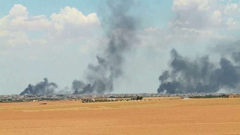 In this Wednesday video grab, smoke rises from Manbij, Syria. U.S.-backed fighters on Thursday closed all roads leading to the town, an IS-group stronghold, and surrounded it from three sides. Photo: Anonymous, TEL / Arab 24