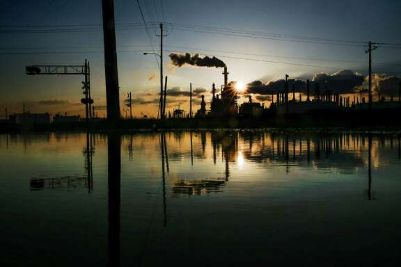 The sun sets behind the LyondellBasell Houston Refinery, one of the businesses on the list of high harm facilities, Thursday, April 14, 2016 in Houston.