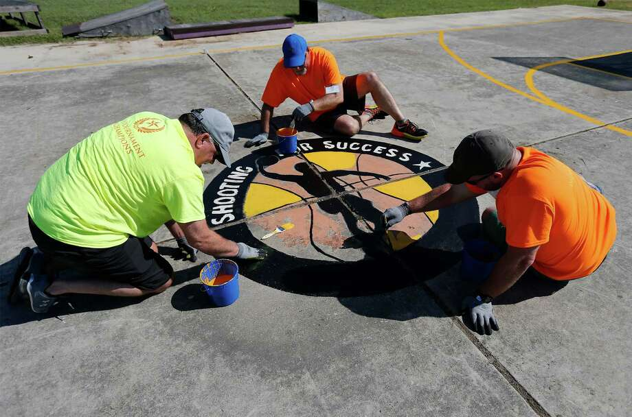 H-E-B employees Matt Serrano (from right), Mark Powers and corporate partner Stacy Wright of Tyson Foods help repaint a basketball court logo as employees and partners join together for the 31st annual H-E-B Tournament of Champions, a major community event which involves service projects across the city on Thursday, June 9, 2016. St. Jude's Ranch for Children was one of the beneficiaries of the event as numbers of volunteers all gathered to refresh the Hill Country campus between Bulverde and Spring Branch. Tasks included painting, landscaping and cleaning the facility which provides for abused, neglected and abandoned children. (Kin Man Hui/San Antonio Express-News) Photo: Kin Man Hui, Staff / San Antonio Express-News / ©2016 San Antonio Express-News