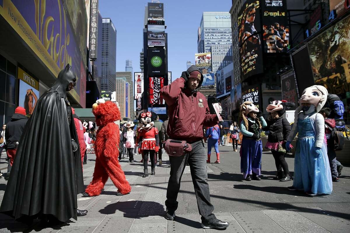 In this March 29, 2016 file photo, a bus tour ticket seller, center, walks through a group of costumed characters in Times Square in New York.