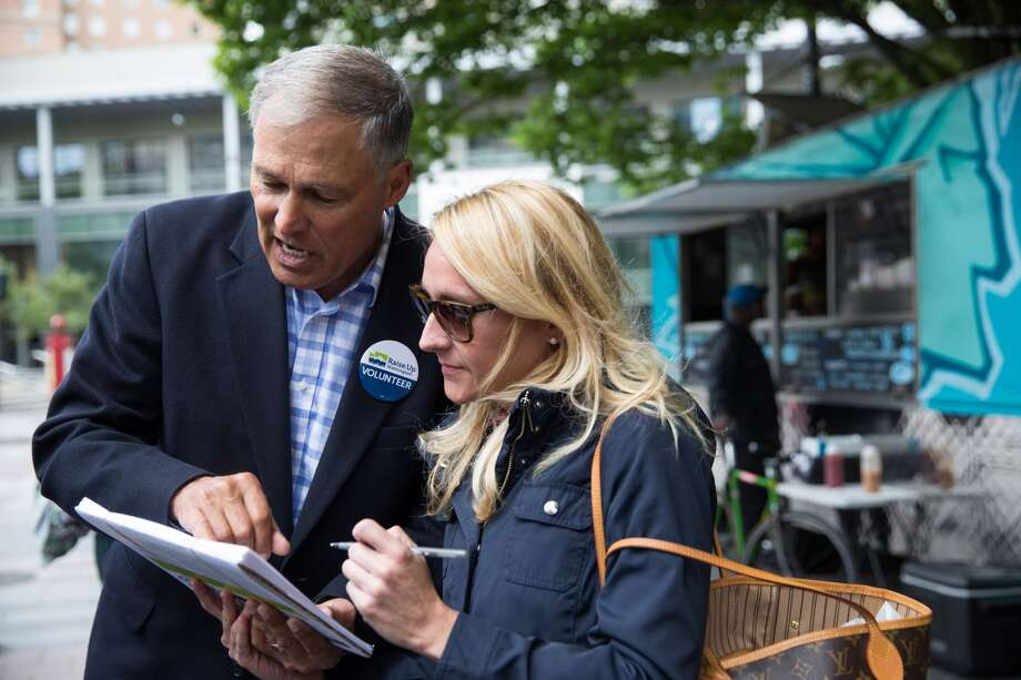 Governor Jay Inslee instructs Jennifer Garvale on how to sign in support of Initiative 1433, a campaign to raise the statewide minimum wage to $13.50, at Westlake Park on Thursday, June 9, 2016.