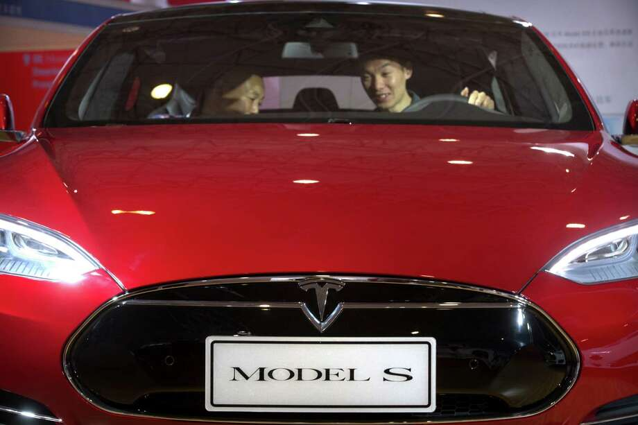 Shoppers in Beijing check out a Tesla Model S this spring. A less expensive version is the Model S 60.  Photo: Mark Schiefelbein, STF / Copyright 2016 The Associated Press. All rights reserved. This material may not be published, broadcast, rewritten or redistribu