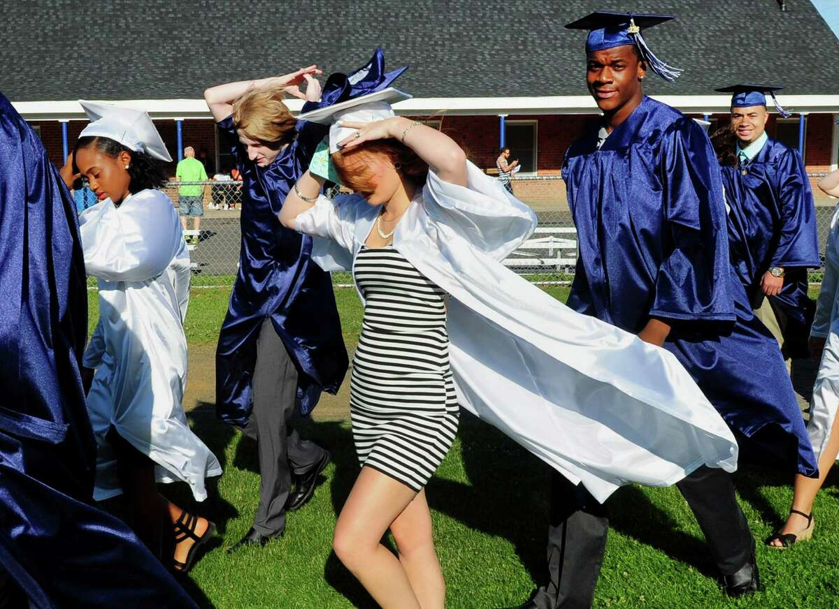 A gust of wind hits graduate Sabrina Fitzgerald as she walks in line with fellow graduates for the start of Ansonia High School's Class of 2016 Commencement Exercises at Nolan Field in Ansonia, Conn., on Thursday June 09, 2016.