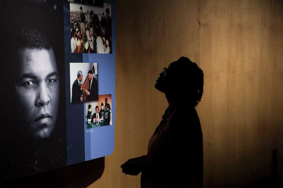 A woman looks at an exhibit in the Muhammad Ali Center in Louisville, Ky., on Thursday. Two days of ceremonies bidding farewell to Ali began with a Muslim prayer service in Louisville. Photo: BRENDAN SMIALOWSKI, Stringer / AFP or licensors
