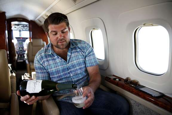 Joe Wagner pours a bottle of sparkling wine while on a private plane flying back to Napa, California, on Monday, April 18, 2016.