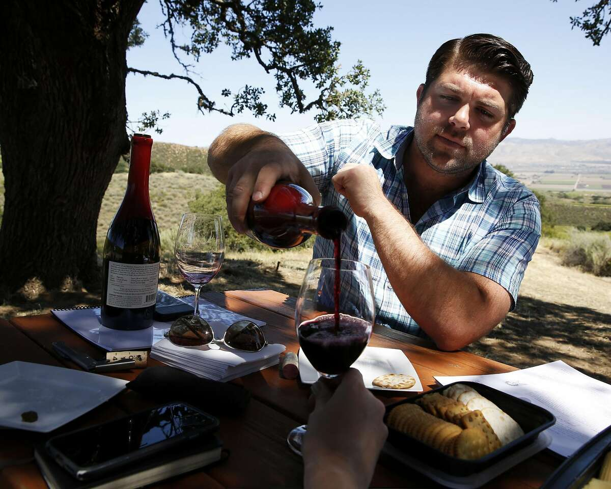 Joe Wagner pours Belle Glos wine during a tasting at a picnic table in the Las Alturas vineyard at the Santa Lucia Highlands in Monterey County, California, on Monday, April 18, 2016.