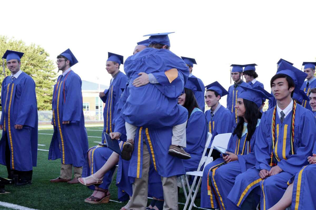 Kyle Bennett jumps into the arms of Daniel Robinson after receiving his diploma during Seymour High School's Commencement ceremony on their campus in Seymour, Conn.. The graduation was held on Thursday June, 9, 2016.