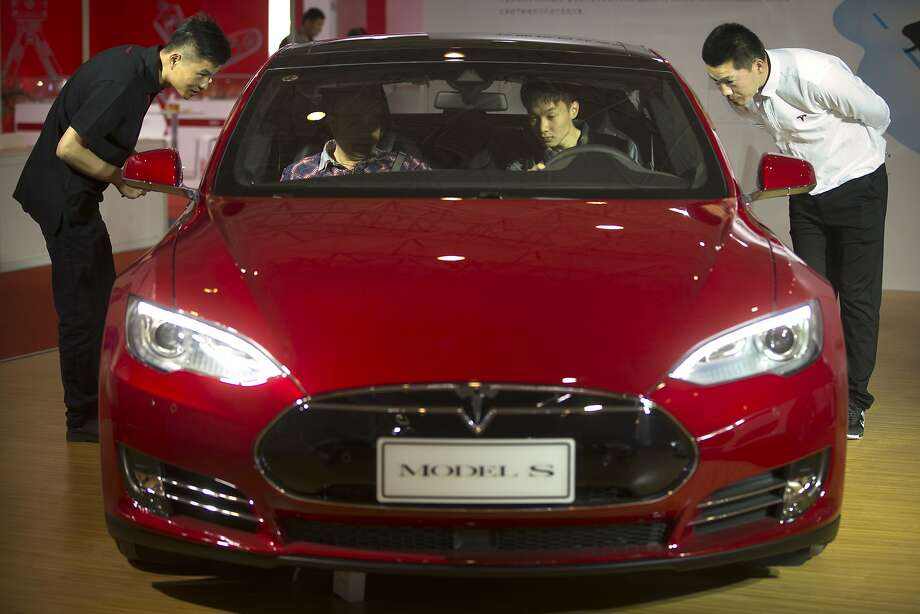 Staff members talk with visitors as they sit inside a Tesla Model S electric car on display at the Beijing International Automotive Exhibition in Beijing, Monday, April 25, 2016. (AP Photo/Mark Schiefelbein) Photo: Mark Schiefelbein, Associated Press