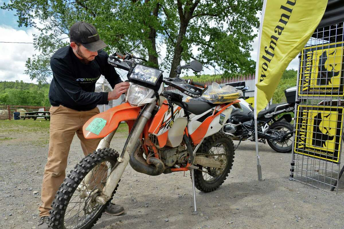 Eric Milano of MotoVermont fits a tank bag to a KTM 200 at Americade's Dirt Daze Thursday June 9, 2016 in Lake Luzerne, NY. (John Carl D'Annibale / Times Union)