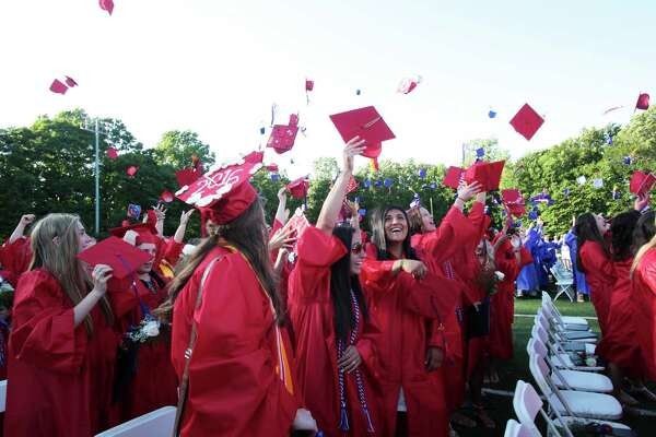 Graduates toss their caps at the Joseph A. Foran High School graduation ceremony in Milford, Conn. on Thursday, June 9, 2016.