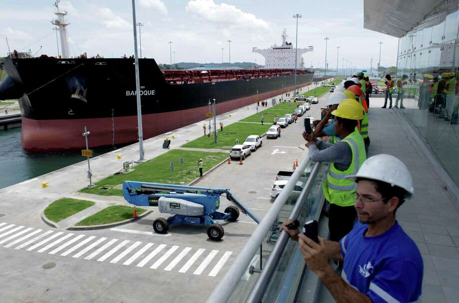Workers take photographs of the Malta flagged cargo ship named Baroque, a post-Panamax vessel, as it navigates the Agua Clara locks during the first test of the newly expanded Panama Canal in Agua Clara, Panama, Thursday, June 9, 2016. The canal's expansion project will be inaugurated on June 26. (AP Photo/Arnulfo Franco) Photo: Arnulfo Franco, STF / Copyright 2016 The Associated Press. All rights reserved. This material may not be published, broadcast, rewritten or redistribu